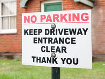 A sign outside a house saying no parking keep driveway entrance Stock Photos