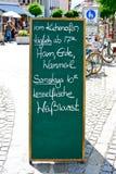 Sign outside a restaurant advertises menu items. A sign outside a restaurant in Murnau,Germany,advertises menu items for lunch and dinner Stock Photo