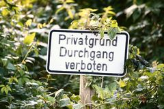 Sign in an overgrown place in Germany. It says Private property, no trespassing Stock Photography