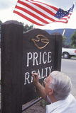 A sign painter touching up his work, Stock Photo