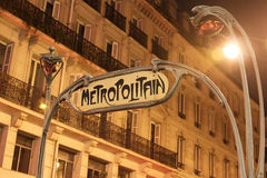 Sign of the Paris subway. Art Deco sign of the Paris metro at night, yellowish traffic light Royalty Free Stock Photos