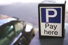 Sign for parking in London. Sign of parking fees in London. Black car stands next to sign Stock Images
