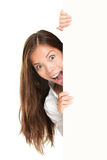 Sign people - woman peeking. Out from behind billboard paper poster. Excited woman looking surprised at camera. Beautiful brunette with long hair. Asian stock images