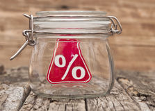 Sign percent in a glass jar. On wooden table Royalty Free Stock Photo