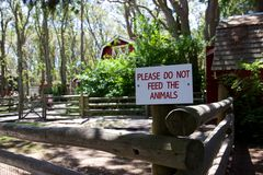 Sign in petting zoo: Do not feed the animals. A sign in the petting zoo at Victoria, Canada's Beacon Hill Park reads Please Do Not Feed the Animals. Farm scene Stock Image