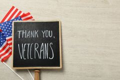 Sign with phrase Thank You, Veterans and American flags on white wooden table, flat lay. Space for text