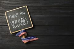 Sign with phrase Thank You, Veterans and ribbon on black wooden table, top view. Space for text