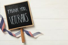 Sign with phrase Thank You, Veterans and ribbon on white wooden table, flat lay. Space for text