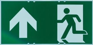 Sign with the pictogram of a walking person and an arrow in white on a green background, indication of an escape route in case of. Danger, abstract stock photography