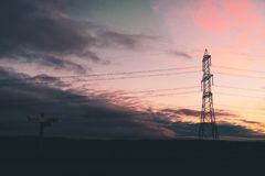 A power pylon stands beside a wooden sign royalty free stock photos