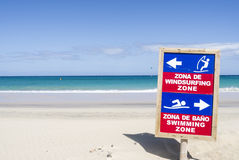 Sign post beach swimmer sports. Sign post at a sandy beach marking zones for swimmers and surfer Stock Photos