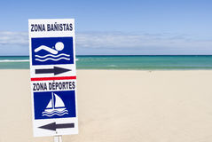 Sign post beach swimmer sports. Sign post at a sandy beach marking zones for swimmers and surfer Stock Photo