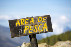 Sign post showing the free fishing area at a campsite in Merida,. Spanish wooden sign post showing the free fishing area near the river in the mountains of royalty free stock photography