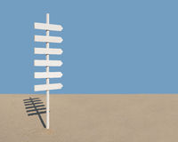 Sign post with six arrows on sandy beach Stock Photo