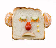 Sad bread face with fruit and vegetables. Funny sad face made using bread, fruit and vegetables Royalty Free Stock Images