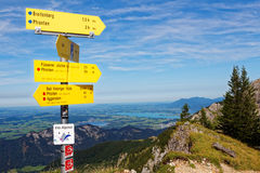 Signpost on mountain top panoramic view. Signpost on a mountain ridge in the alpine region of Allgau showing the distance to different destinations. View to Stock Photography