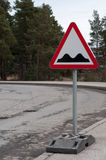 Sign and potholes on the road Royalty Free Stock Images