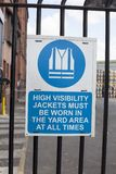 A sign on in the production company high visibility jacket must Stock Photography