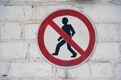 The sign of passage is forbidden to people against a white brick wall. stock photo