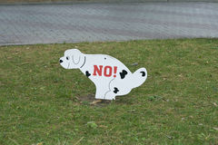 Sign prohibiting dog walking on the lawn. The sign depicts a white dog that tries to go to the toilet. It says NO. This means that dogs and other animals royalty free stock photography