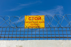 Sign prohibiting passage. On the fence with barbed wire Stock Image