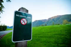 A sign prohibiting the use of drone in front of a mountain. stock images