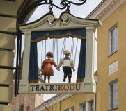 Sign of puppet theater. Wooden figures of the sailor and his girl on a sign of puppet theater Stock Photos