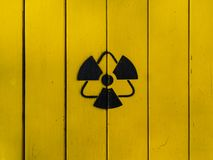 Sign of radiation on a yellow wooden board. Radioactive sign - symbol of radiation. Yellow and black radioactive hazard ionizing radiation nuclear danger stock images