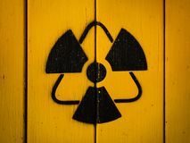Sign of radiation on a yellow wooden board. Radioactivity sign, close-up. Sign of radiation on a yellow wooden board. Radioactive sign - symbol of radiation royalty free stock photo