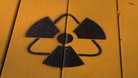 Sign of radiation on a yellow wooden board.