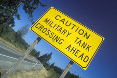 A sign that reads �Caution - Military tank crossing ahead� Stock Photography