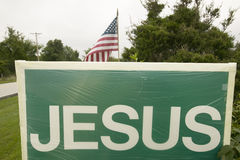 A sign reads Jesus promoting the Christian point of view alongside an American Flag, representing the separation of Church and Sta Stock Photography