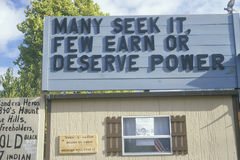 A sign that reads Many seek it, few earn or deserve power Stock Photo
