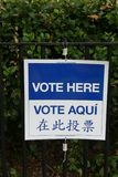 Vote Here. A sign that reads `Vote here` in English, Spanish and Chinese, outside a voting booth in New York City Stock Photography