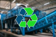 Sign recycling waste. The waste sorting and processing plant is blurry in the background.  Royalty Free Stock Images