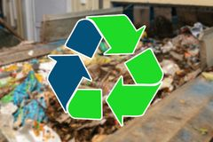 Sign recycling waste. The waste sorting and processing plant is blurry in the background.  stock photos