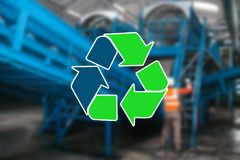 Sign recycling waste. The waste sorting and processing plant is blurry in the background.  royalty free stock photo
