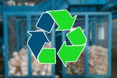 Sign recycling waste. The waste sorting and processing plant is blurry in the background.  Stock Image
