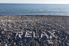 The sign Relax made from white pebbles on pebble beach on the se. A Royalty Free Stock Photography