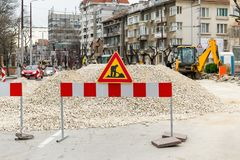 The sign of road works on red white barrier in front of a pile of gravel on a city street. Construction and repair of asphalt royalty free stock image