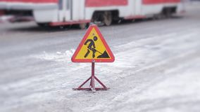 Sign Road works is on the roadway in the winter. Cleaning of streets after a snowfall. Snowplows in the city. Close-up of the sign Road works, in the background stock video footage