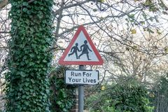 Sign Run For Your Lives. Children Crossing warning street sign with added unoffical sign with text Run For Your Lives, in rural town in Sussex, England Royalty Free Stock Photography