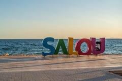 Sign Salou at the coastline Costa Dorada, Spain. Summertime sunset.