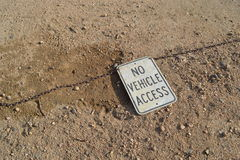 A Sign in the Sand. This sign says no vehicle access.   It is in the sand at a baseball field in Colorado Royalty Free Stock Photography