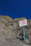 A sign saying Beware of falling rocks! Bathing is prohibited. Steep mountain slopes. A sign saying Beware of falling rocks! Bathing is prohibited. against the Royalty Free Stock Photo