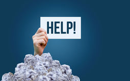 A sign saying help in a pile of garbage. royalty free stock photos