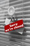 Sign saying. `sorry we`re closed` on a glass door with a white, closed venetian blind. It can be used for business concepts or backgrounds Stock Images