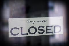 Sign saying sorry we are closed. Behind glass with reflection, selective focus, vintage filter Stock Photo