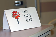 Sign says DO NOT EAT. A sign in a hospital patient's room states STOP, DO NOT EAT Royalty Free Stock Image