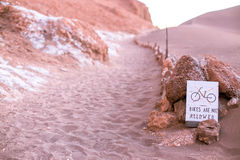 A sign says no bikes are allowed on the dune, moon valley, atacama desert Royalty Free Stock Images